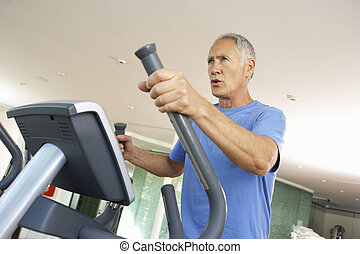Senior Man On Cross Trainer In Gym