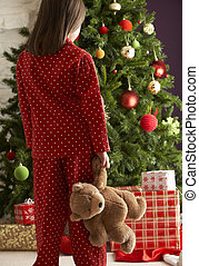 Young Girl Standing With Teddy Bear In Front Of Christmas Tree