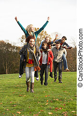 Group Of Teenage Friends Having Piggyback Rides In Autumn...
