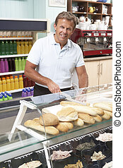Man Working Behind Counter In Caf