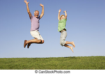 Senior man with grandson jumping in air