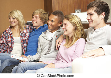 Group Of Teenage Friends Sitting On Sofa At Home Watching TV
