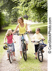 Mother and children riding bikes in countryside