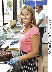 Woman Working Behind Counter In Caf Slicing Cake