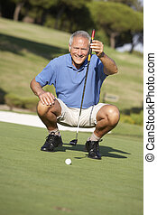 Senior Male Golfer On Golf Course Lining Up Putt On Green