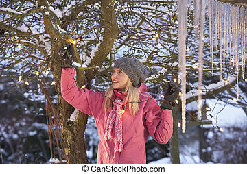 Teenage Girl Hanging Fairy Lights In Tree With Icicles In Foreground