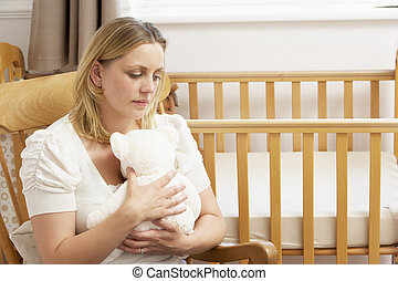 Sad Mother Sitting In Empty Nursery