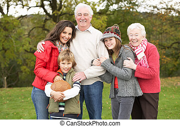 Grandparents With Grandchildren And Mother Holding Football...