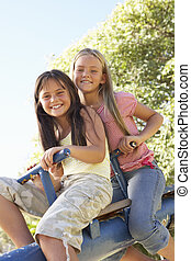 Two Girls Riding On See Saw In Playground