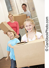 Family happy on moving day carrying cardboard boxes