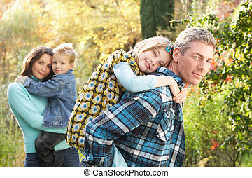 Family Group Outdoors In Autumn Landscape With Parents Giving Chiildren Piggyback
