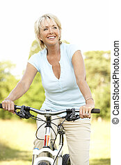 Portrait of mature woman riding cycle in countryside