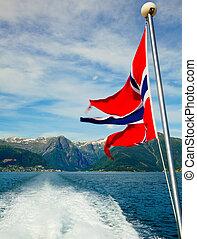 Norwegian flag against fjord mountains