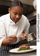 Chef Adding Sauce To Dish In Restaurant Kitchen