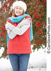 Senior Woman Standing Outside In Snowy Landscape