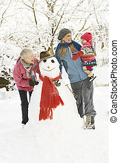 Young Girl With Grandmother And Mother Building Snowman In Garden