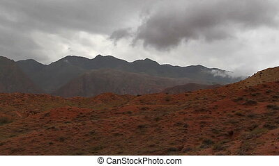 Red mountain - Timelaps. clouds quickly run over the red...