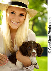 Smiling female holding her puppy - Young female sitting with...
