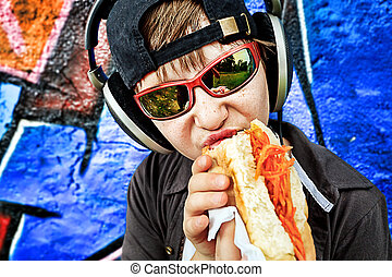 eating - Portrait of a modern boy teenager eating hot dog...