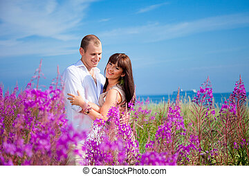 Romantic couple among purple flowers near blue sea - Loving...