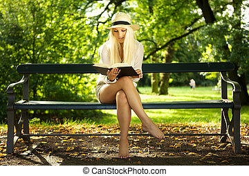 Beauty sitting on a bench reading in the sun