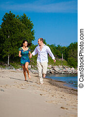 Enamored young man and girl running on sandy beach along...