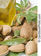 Oil, almonds and leaves. - Almonds and a bottle of almond...