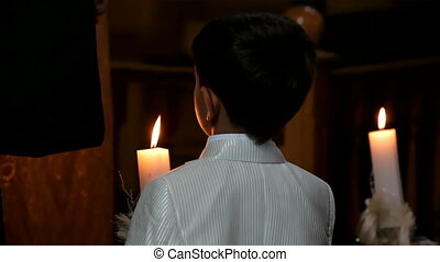 Believer boy - A boy prays in a church holding a candle.