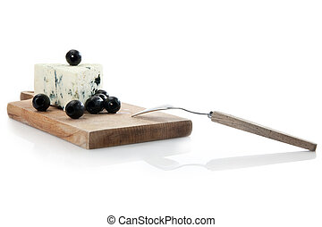blue cheese on cheeseboard decorated with black olives