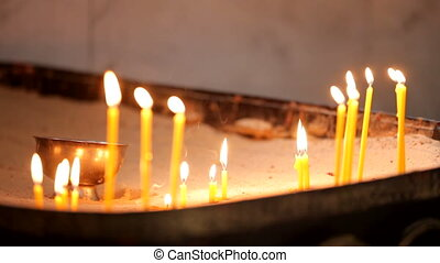 Sacred rite - A few candles sticking out of the sand.