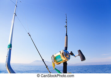 fishing boat trolling with outrigger gear and golden reel...