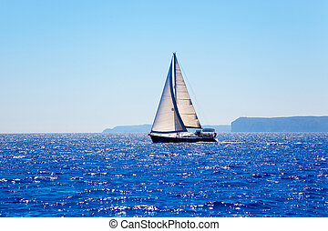 Blue Mediterranean sailboat sailing in perfect ocean at San...