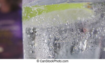 Sparkling water w/ lime slice. - Closeup of a cold and...