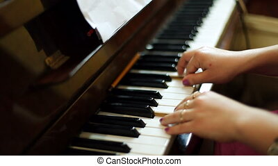 Womens hands play the piano - A woman plays the piano.