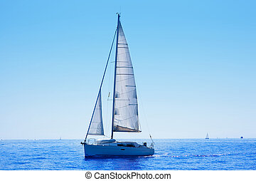 blue sailboat sailing mediterranean sea with water horizon