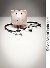 Piggy Bank and Stethoscope with Selective Focus on a...