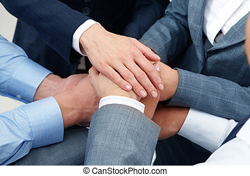 Unity - Image of business people hands on top of each other...