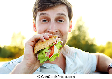 Young man eating sandwich in the park