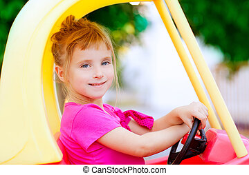 blond children girl driving toy car yellow