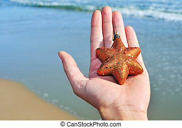christmas on the beach - a golden christmas star on a hand...