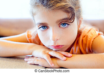 Blue eyes sad children girl crossed arms on table