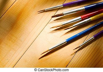 Paintbrushes isolated on wooden background