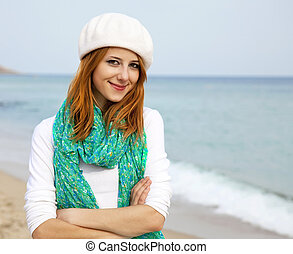 Young beautiful girl sitting at the beach