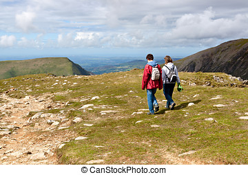 Two hikers walking on Snowdonia, Wales, UK