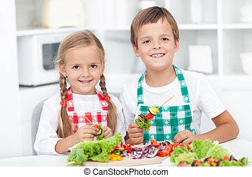 Happy kids preparing a meal in the kitchen - Happy healthy...