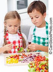 Kids preparing veggies on stick in the kitchen - healthy...
