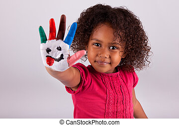 Little African Asian girl with painted hands in colorful...