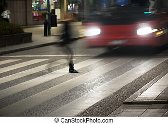 Woman crossing street in front of bus