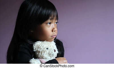 Sad Little Girl Hugging Teddy Bear - A cute little upset...
