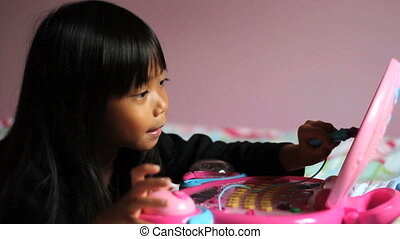 Little Girl Playing On Pink Laptop - A cute little Asian...